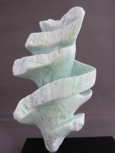 Wokkel heet dit beeldje van Aziatische speksteen. De vorm is geinspireerd op de wokkel en het is dus min of meer spiraalvormig. De kleur van de steen is zachtgroen.